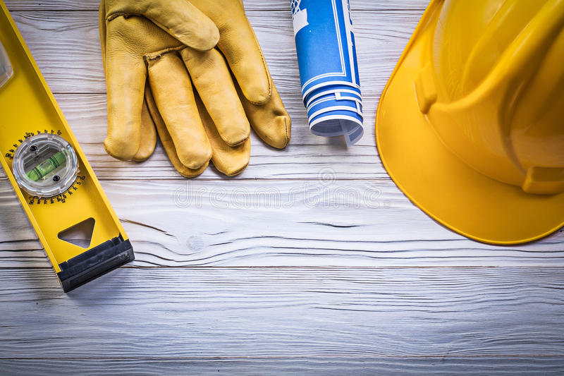 Assortment of working gloves hard hat blue rolled blueprints con. Struction level on wooden board royalty free stock photo