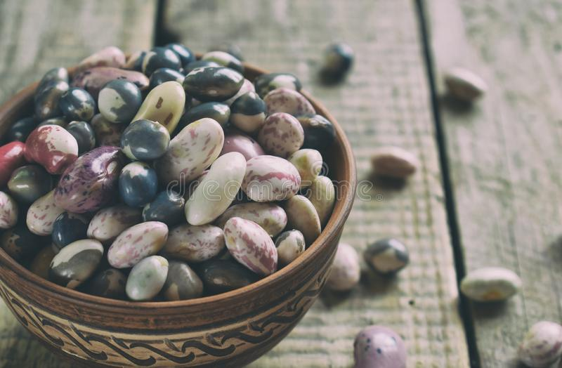 Assortment of young legumes and beans of different varieties and colors in a clay bowl. Raw food. Healthy diet concept. Selective. Focus stock images