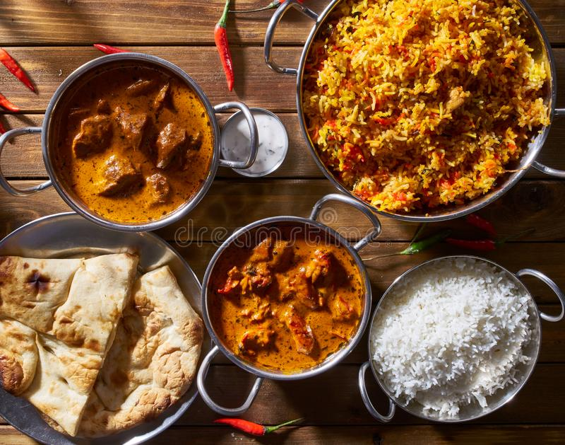 Assortmnent dei piatti indiani compreso, del pollo del burro, del masala di tikka dell'agnello, del biryani con naan e del raita fotografia stock libera da diritti