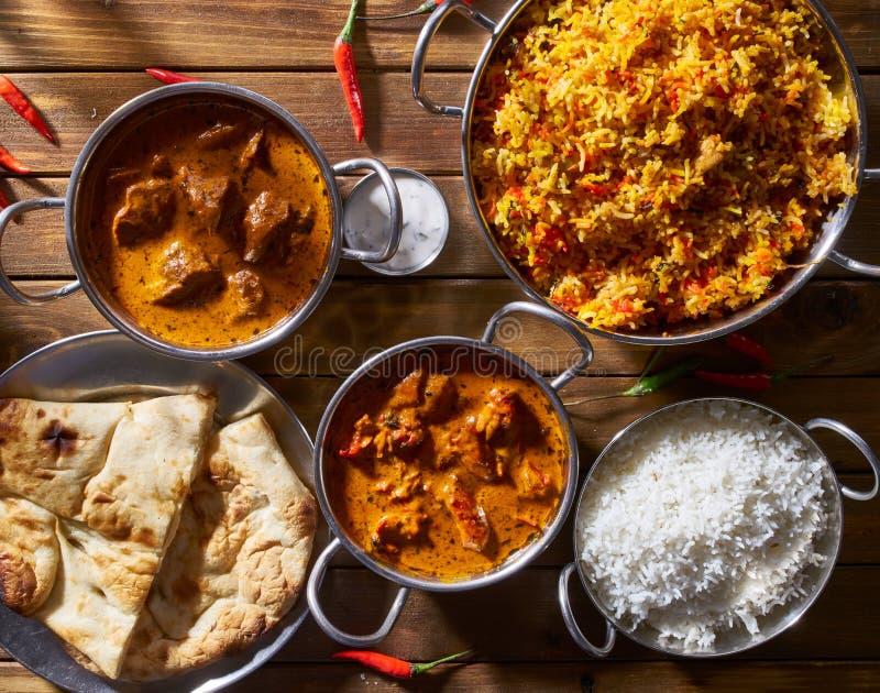 Assortmnent des plats indiens comprenant, du poulet de beurre, du masala de tikka d'agneau, du biryani avec naan et du raita photo libre de droits