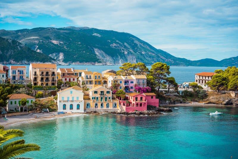 Assos村庄 对生动的五颜六色的房子的美丽的景色在蓝色绿松石附近上色了透明海湾盐水湖 Kefalonia 免版税库存照片