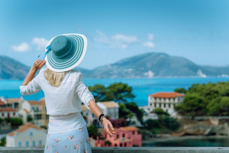 Assos dans la lumière de matin Jeune femme de touristes portant les vêtements bleus de chapeau de soleil et de blanc admirant la  image libre de droits