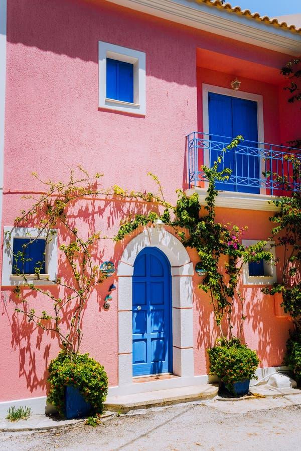 Assos by Traditionella rosa färger färgade det grekiska huset med den ljusa blåa dörren och fönster Den Fucsie växten blommar omk royaltyfri foto