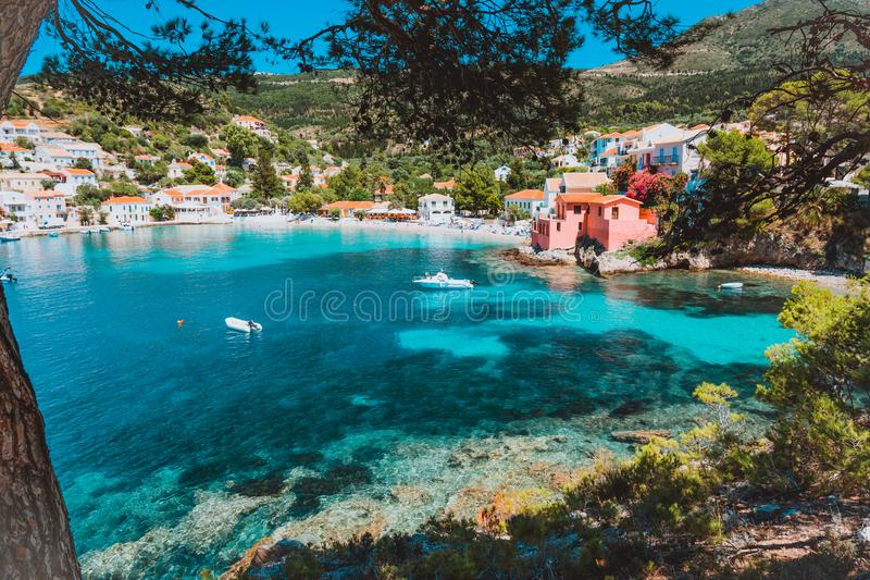 Assos village, Kefalonia, Greece. View on tourquise transparent water framed between green pine grove branches. Deep. Dark pattern on lagoon bottom royalty free stock image