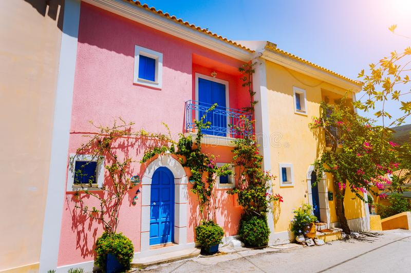 Assos village. Traditional colored greek houses with bright blue doors and windows. Blooming fucsia plant flowers royalty free stock photos