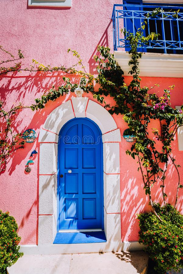 Assos village. Traditional lilac colored greek house with bright blue door and fucsie plant flowers around. Kefalonia stock photos
