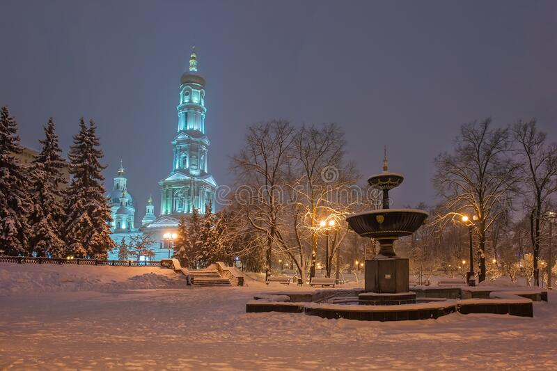 The Assumption cathedral and fountain in the park on winter evening. Kharkiv, Ukraine.  stock photos