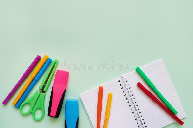 Assuntos de escola em um fundo verde Bloco de notas, tesouras coloridas e penas de ponta de feltro De volta ao conceito da escola fotos de stock royalty free