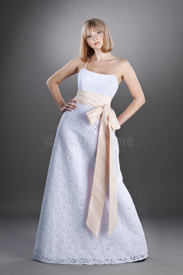 Assured bride in wedding gown. Assured bride wearing wedding gown on studio neutral background royalty free stock images