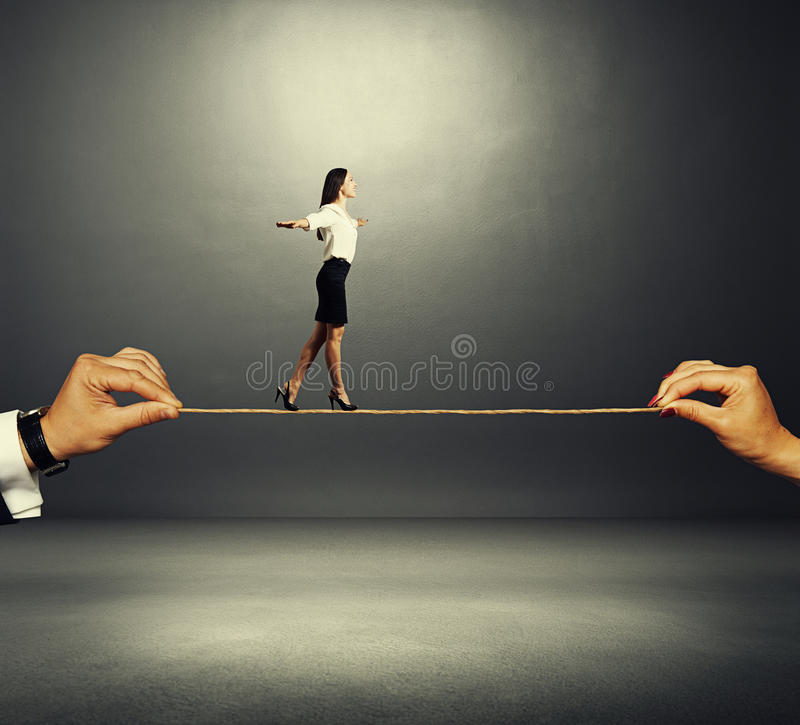 Assured woman walking on the rope. Assured smiley woman walking on the rope over dark background royalty free stock image