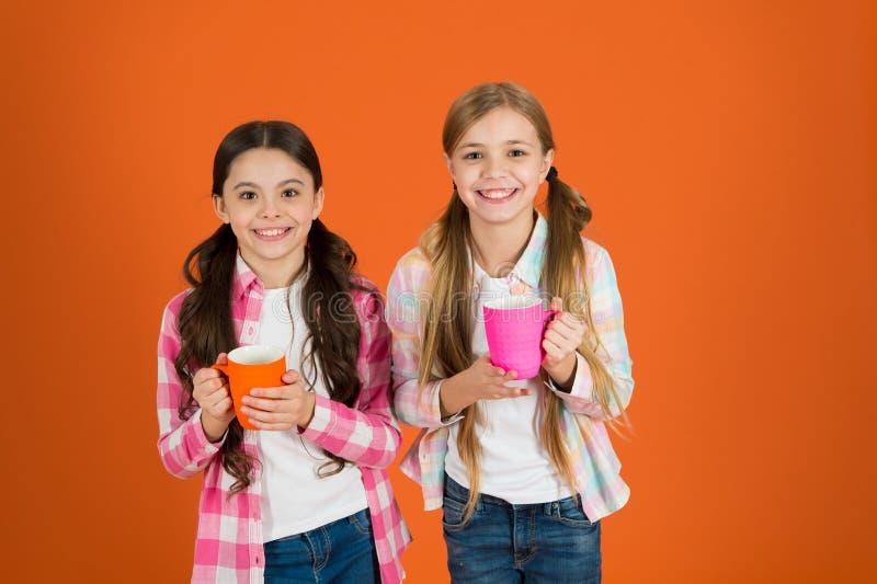 Assurez-vous que les enfants boivent assez d'eau Les enfants de filles tiennent le fond orange de tasses Les soeurs tiennent des  photos stock