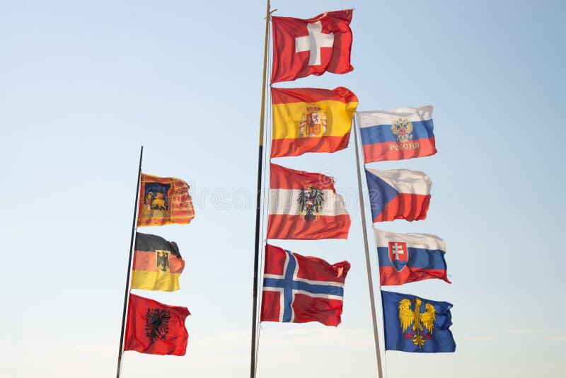 Asta de bandera con las banderas en el viento Banderas de: Región de Véneto, Alemania, Albania, Suiza, España, Austria, Noruega,  fotos de archivo libres de regalías