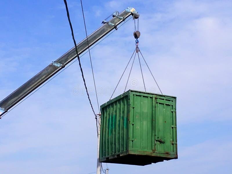 Asta grigia con il gancio blu del contenitore di carico verde dell'ascensore del manipolatore del camion su immagini stock
