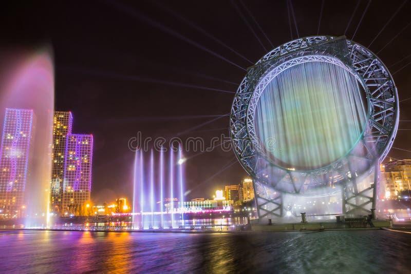 Astana, Καζακστάν - 28 Αυγούστου 2016: Η μουσική πηγή ήλιων παρουσιάζει στο ανάχωμα ποταμών Ishim με τα κτήρια στο υπόβαθρο στοκ φωτογραφία