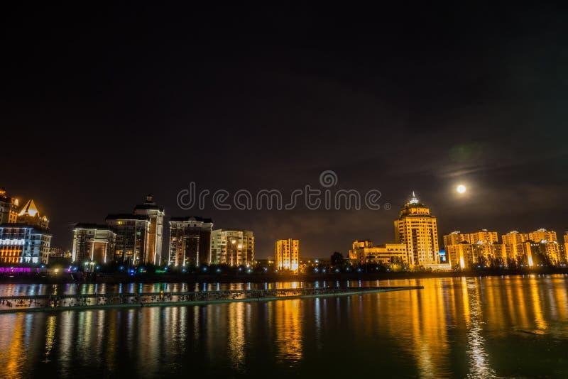 astana Kazakhstan Ishim rzeczny bulwar w księżyc nocy z budynkami i odbicie w wodzie zdjęcie stock