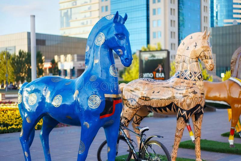 ASTANA, KAZAKHSTAN - JULY 25, 2017: Art installation with figures of horses painted in different ethnic ornament in Astana. Art installation with figures of stock image