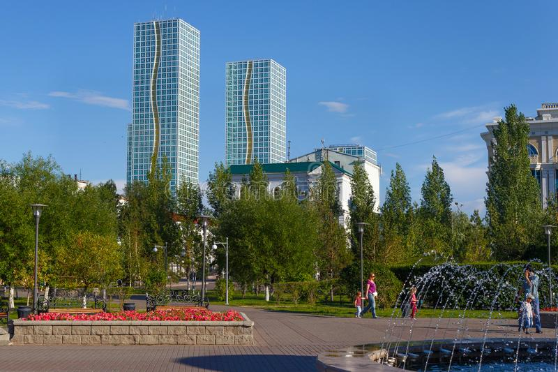 ASTANA, KAZAKHSTAN - JULY 25, 2017: View of the green park in the center of Astana with high-rise buildings on the background. royalty free stock images