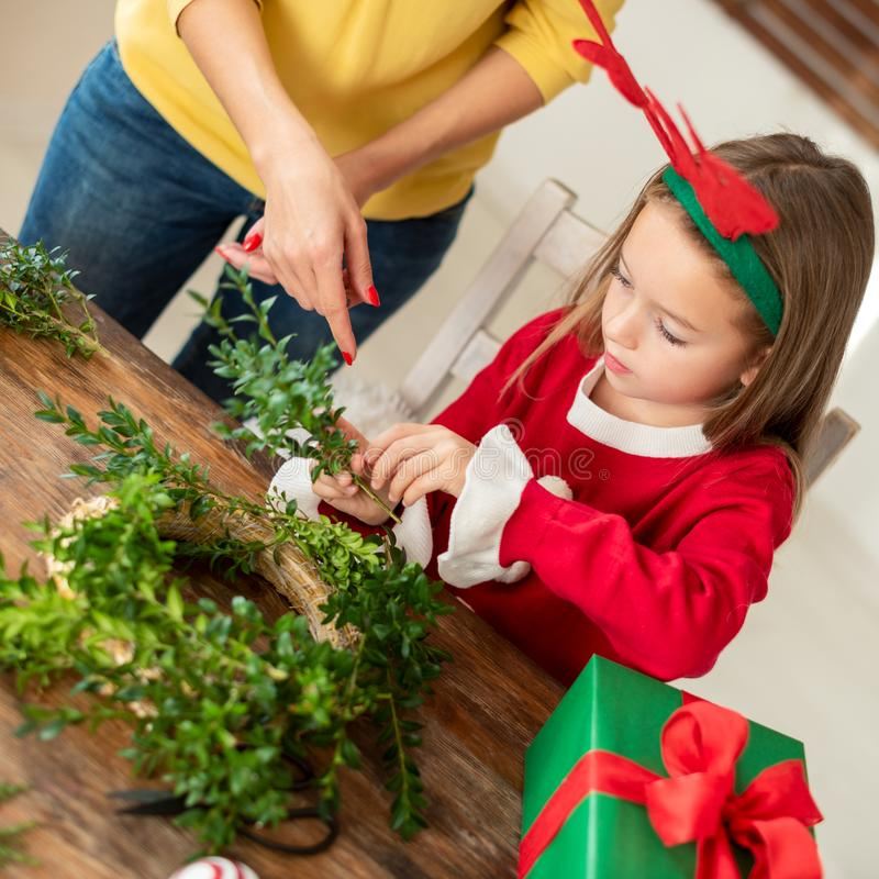 Astas del reno de la muchacha linda del preescolar que llevan y su madre que hacen la guirnalda de la Navidad en sala de estar Di fotografía de archivo libre de regalías