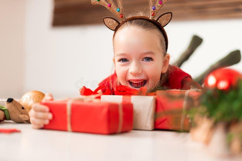Astas del reno del traje de la chica joven que llevan linda que mienten en el piso, rodeado por muchos regalos de Navidad, gritan foto de archivo