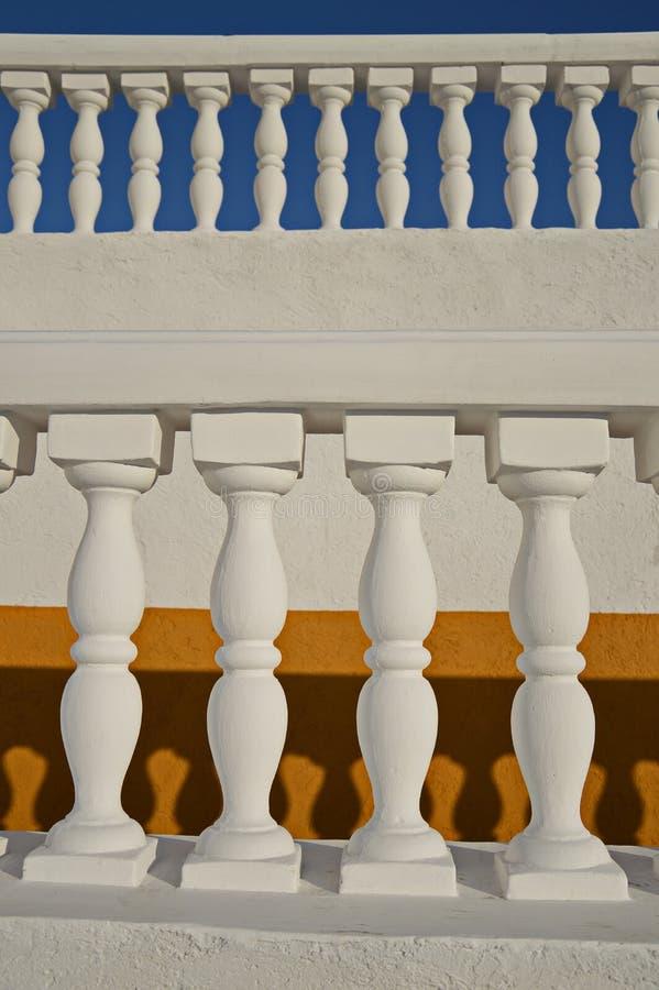 Aste della ringhiera bianche sugli ambiti di provenienza gialli e blu fotografia stock libera da diritti