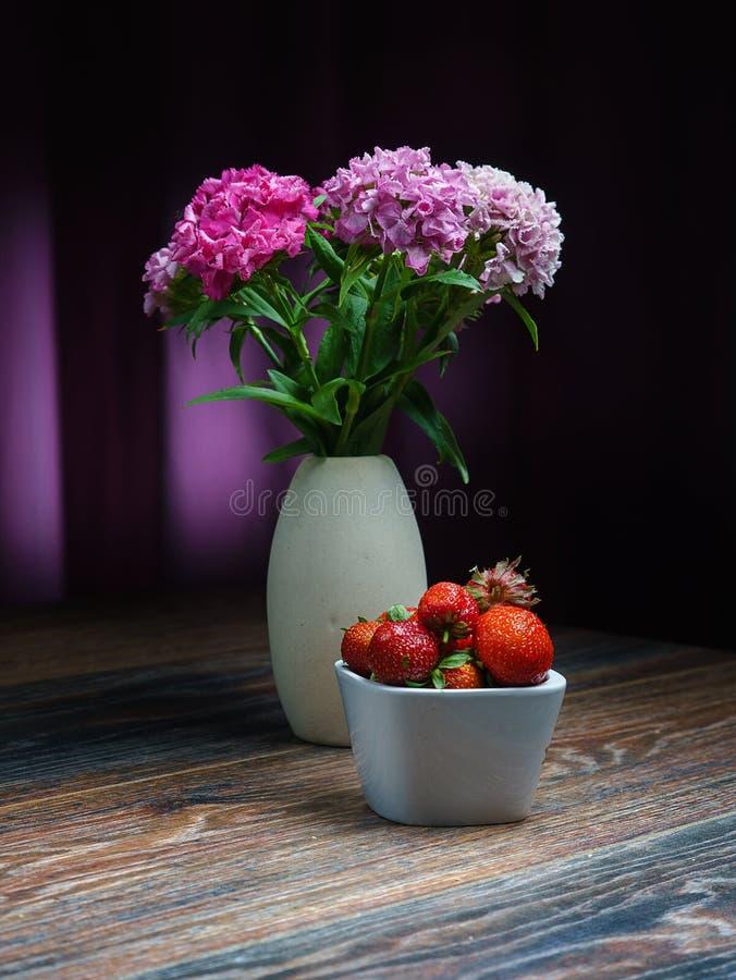 Aster di quae della porpora, è una natura morta con gli aster sereni e fragole fresche, su una tavola di legno, con un fondo sere immagini stock