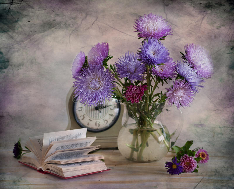 Asters. Bouquet of blue asters, clock and book on a table royalty free stock image