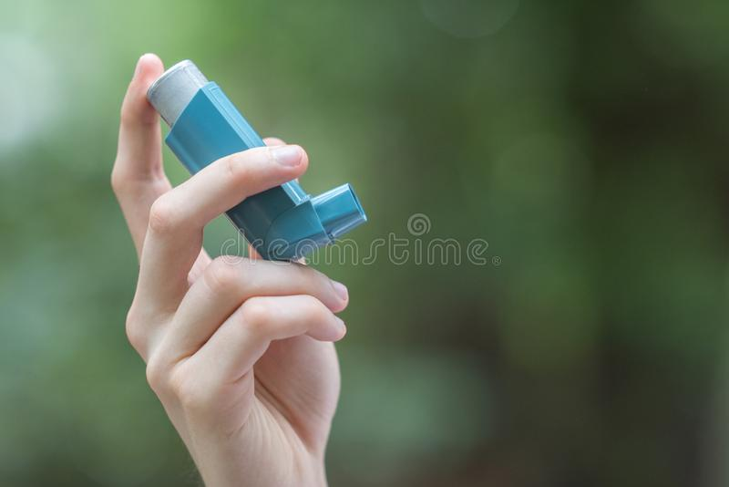 Asthma medecine inhaler holded by a man. During spring time in Tokyo royalty free stock image