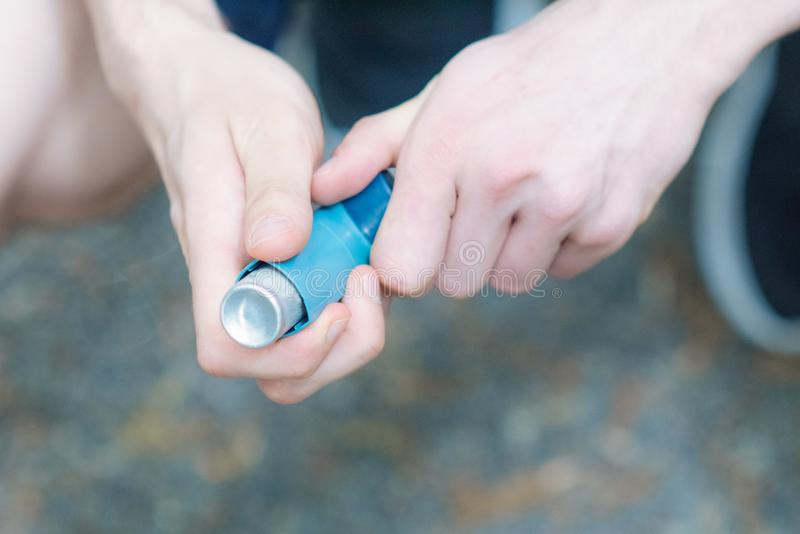 Asthma medecine inhaler holded by two hands of a man. During spring time in Tokyo stock photography