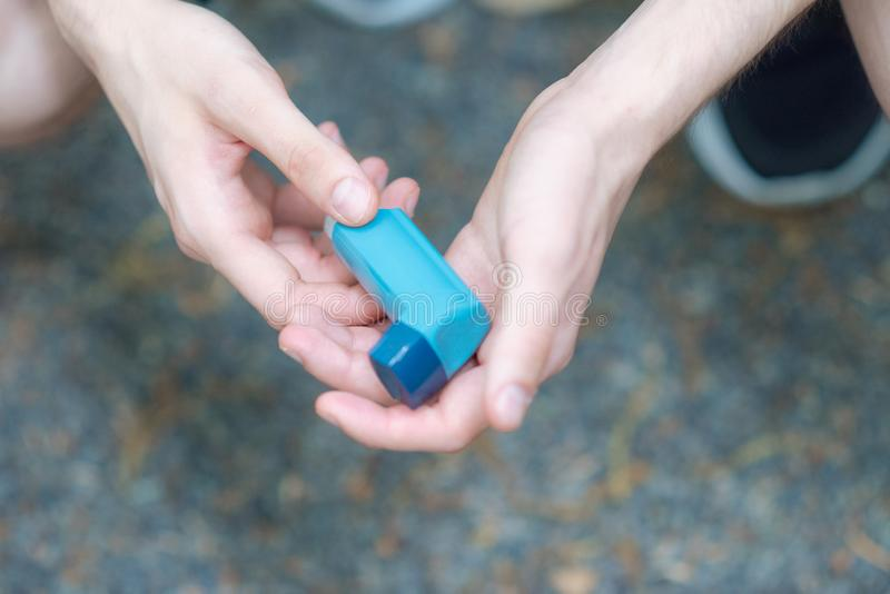 Asthma medecine inhaler holded by two hands of a man. During spring time in Tokyo stock photos