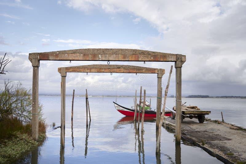 Astillero viejo en la laguna con el barco rojo en la entrada foto de archivo