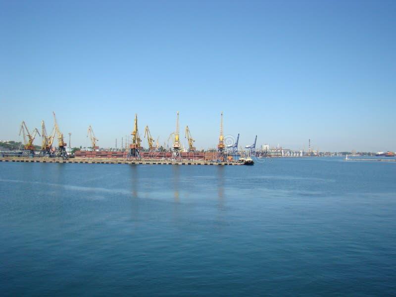 Astilleros en el puerto contra el mar azul fotografía de archivo