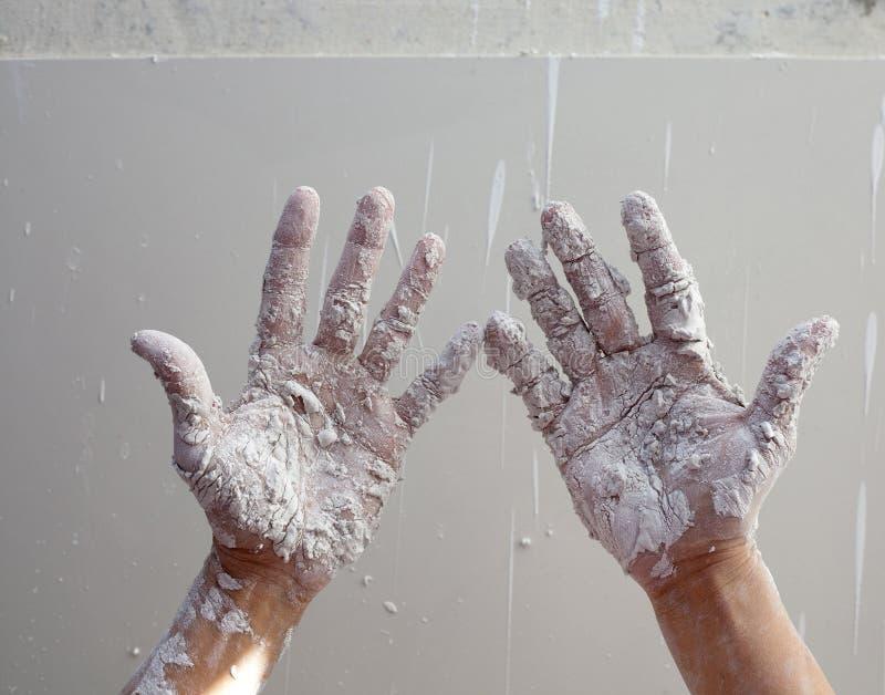 Astist plâtrant des mains d'homme avec le plâtre criqué photographie stock