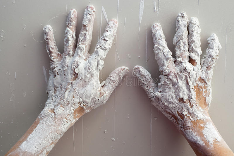 Astist plastering man hands with cracked plaster stock images