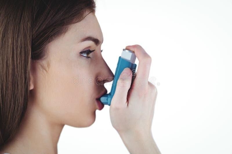 Astmatisk brunett genom att använda hennes inhalator fotografering för bildbyråer