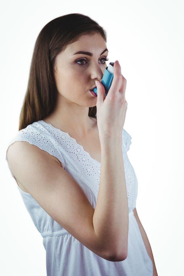 Astmatisk brunett genom att använda hennes inhalator arkivbild