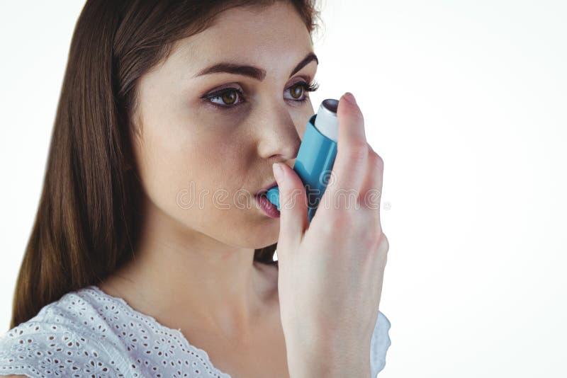 Astmatisk brunett genom att använda hennes inhalator royaltyfria bilder