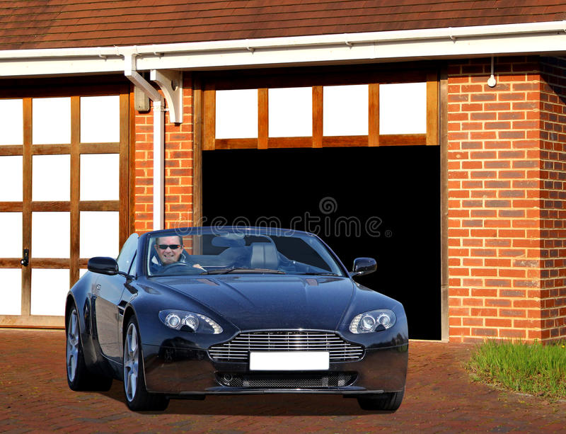 Aston martin vanquish on drive. Photo of a man at home on drive sitting in his luxury aston martin vantage roadster convertible ready for a drive round the royalty free stock photos