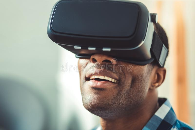 Astonished afro american man getting VR experience. New impressions. Low angle of charming afro american man wearing VR headset and opening mouth royalty free stock images