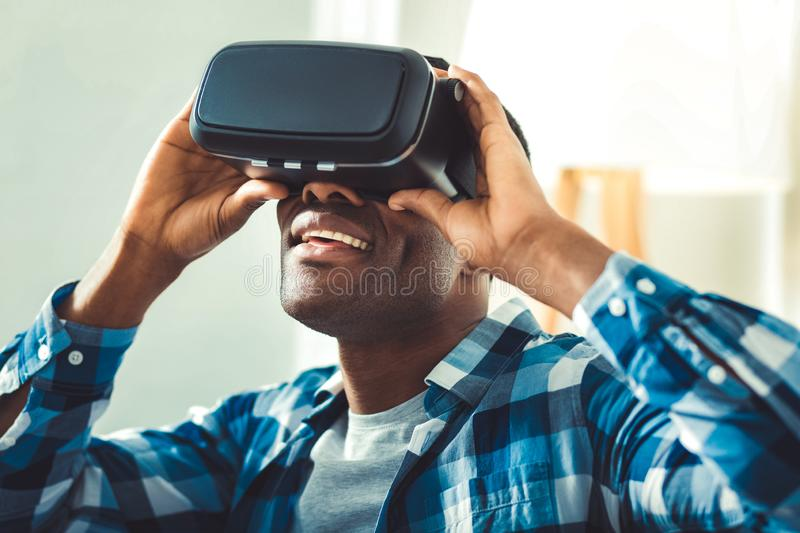 Astonished afro american man surfing in VR. Amazing functions. Amazed afro american man putting on VR glasses and looking up royalty free stock images