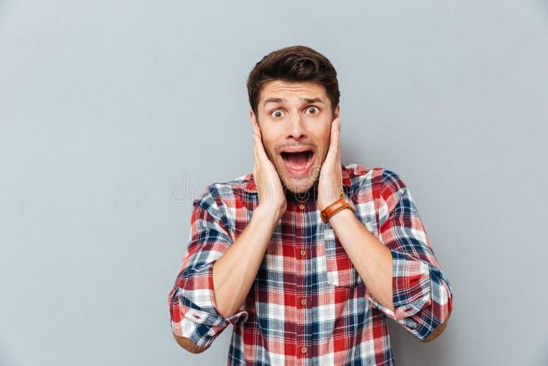 Astonished chocou o homem novo na posição quadriculado e na gritaria da camisa fotografia de stock royalty free