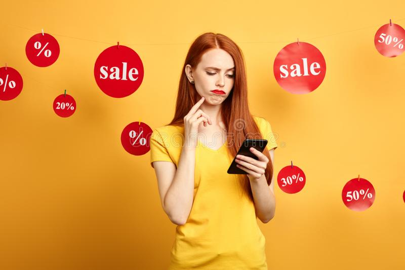 Astonished confundiu a mulher que olha a tela do smartphone foto de stock