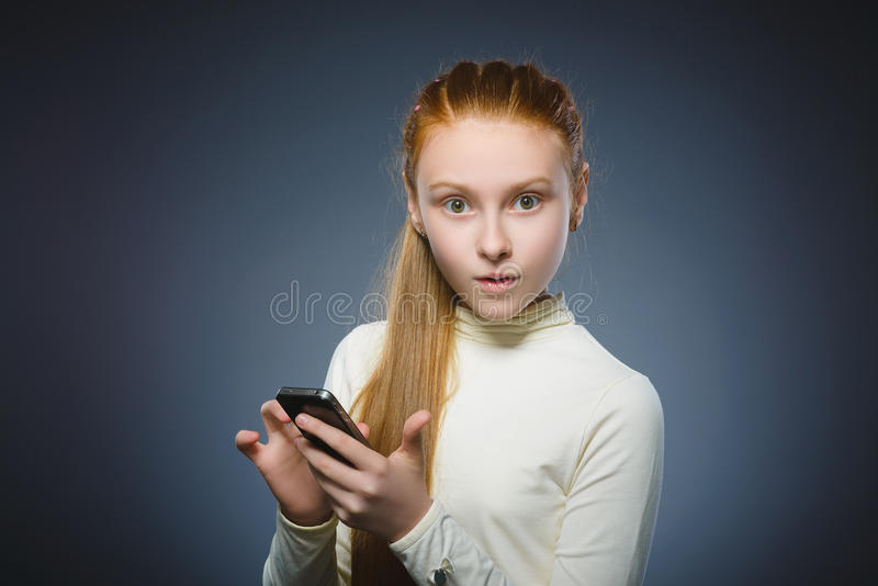 Astonished cute redhead girl with cell phone. isolated on gray stock photo