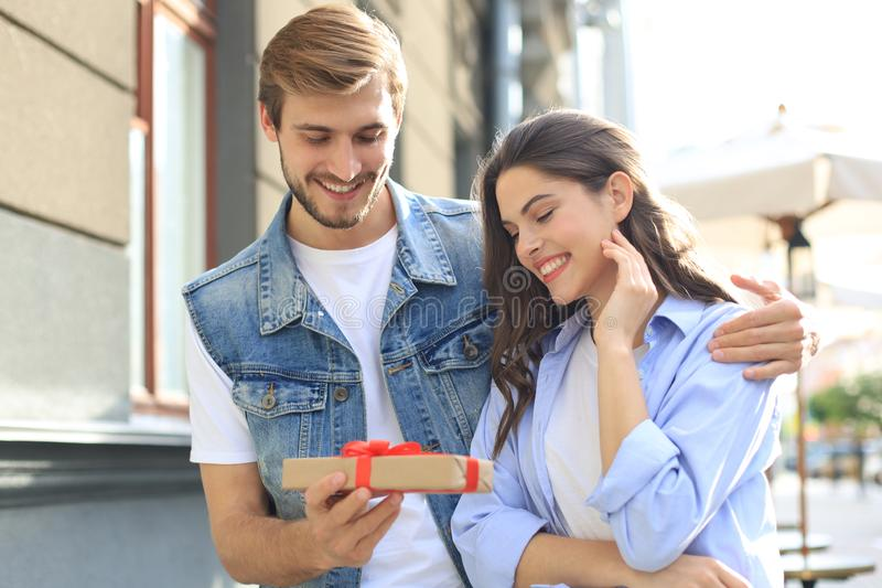 Astonished excited couple in summer clothes smiling and holding present box together while standing on city street. stock image