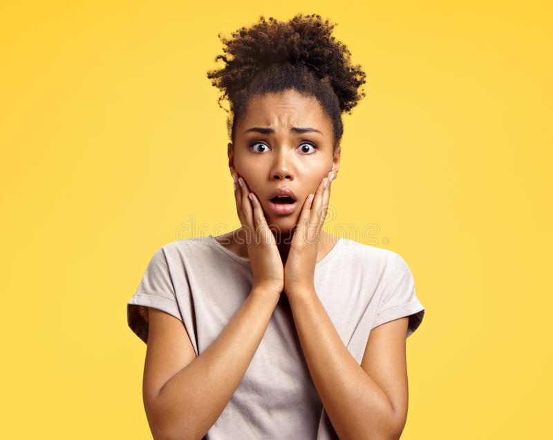 Astonished girl with big eyes, opens mouth widely, keeps hands on cheeks. Photo of african american girl wears casual outfit on yellow background. Emotions and stock image