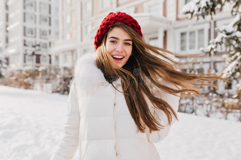 Astonished happy girl in red hat having fun in frozen morning on street full with snow. Expressing positivity, true royalty free stock image