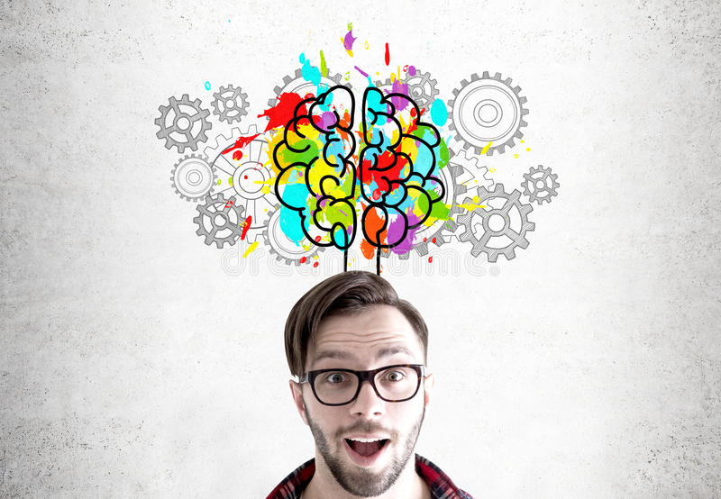 Astonished man, brain and gears. Close up of an astonished bearded young man wearing glasses and standing near a concrete wall with a colorful brain sketch stock photos