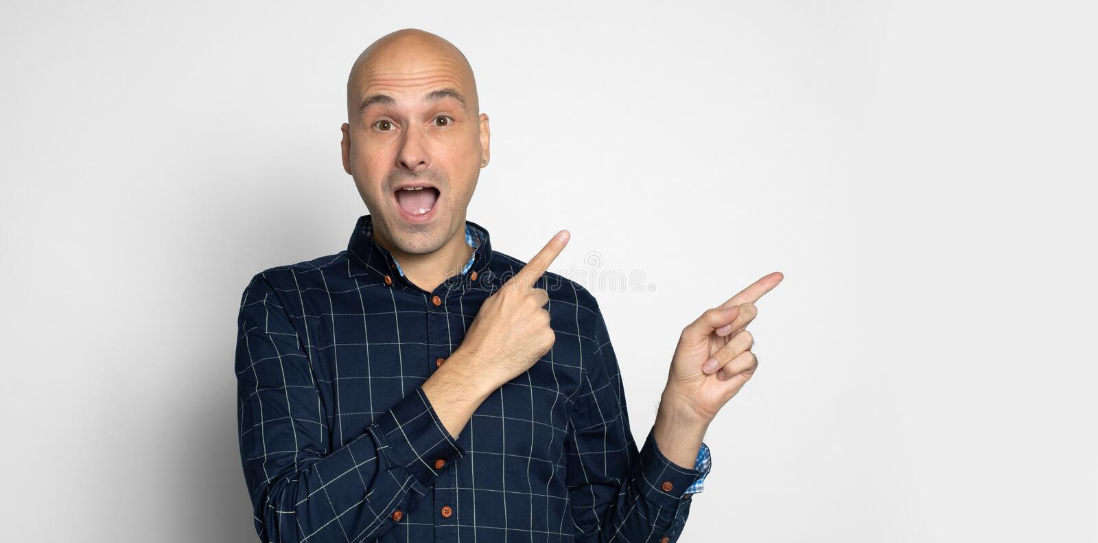 Astonished man pointing his fingers to copy space stock photography