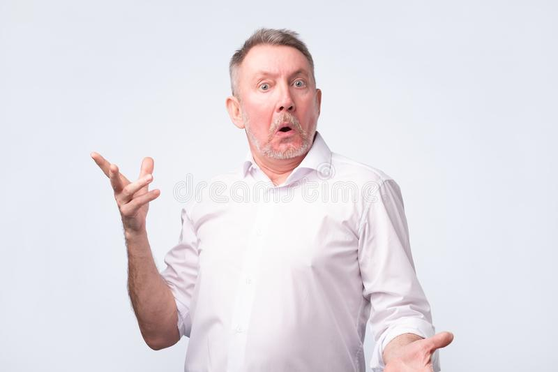Astonished man trying to argue with his wife. stock photos