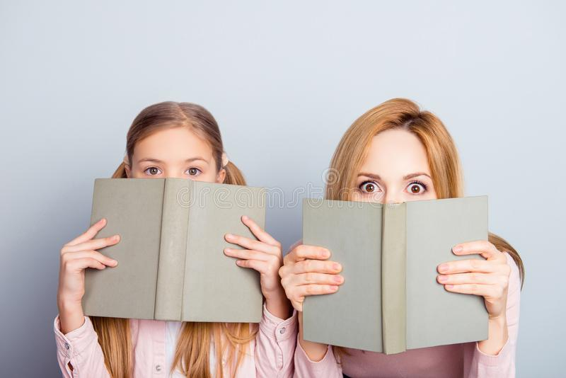 Astonished reaction of mother and daughter close half face with. Books, looking out, wide eyes, impressed by romance, adventure stories, fairy tales, detectives royalty free stock photo