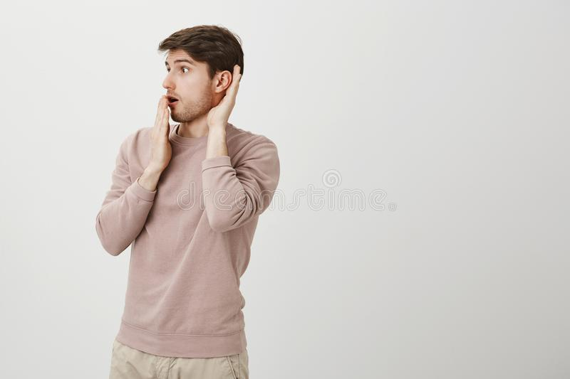 Astonished and surprised handsome male model turned left while holding hands near ear and opened mouth, staring. Somewhere and eavesdropping, standing over gray stock photography